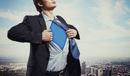 success concept: Image of young businessman showing superhero suit underneath his shirt standing against city background Stock Photo