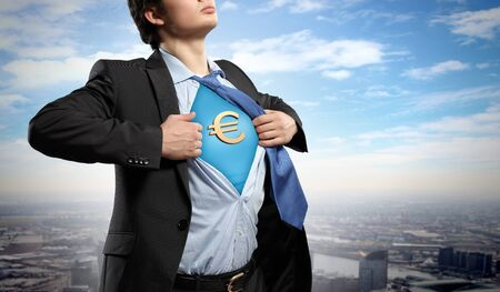 Image of young businessman in superhero suit with euro sign on chest Stock Photo - 17659412