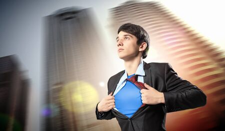 Image of young businessman showing superhero suit underneath his shirt standing against city background Stock Photo - 17659356
