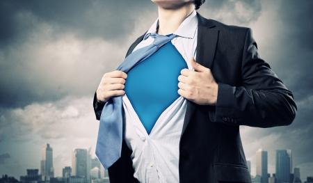 Image de jeune homme d'affaires montrant costume de super-h�ros sous sa chemise debout contre un fond ville Banque d'images