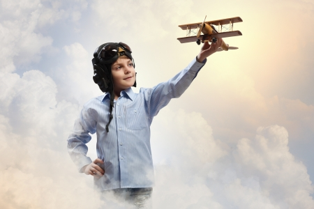 airman: Image of little boy in pilots helmet playing with toy airplane against clouds background