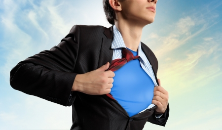 super man: Image of young businessman showing superhero suit underneath his shirt