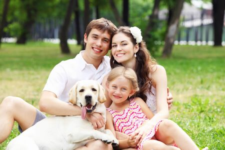 atcamera: Young Family Outdoors in summer park with a dog