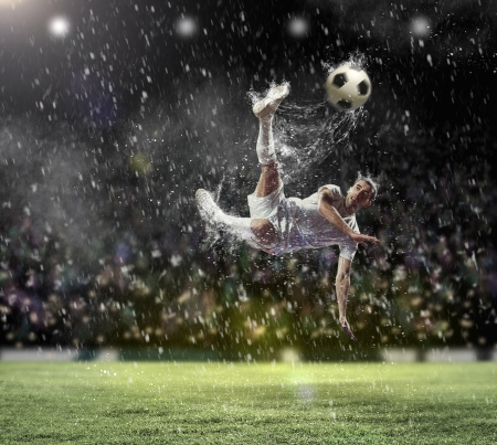 scoring: football player in white shirt striking the ball at the stadium under the rain Stock Photo