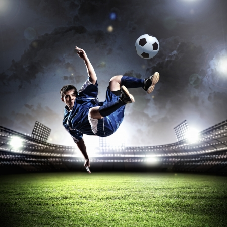 fast foot: football player in blue shirt striking the ball aloft at the stadium