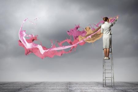 사다리 그리기에 서있는 젊은 여자가 손가락으로 밝아진 스톡 콘텐츠