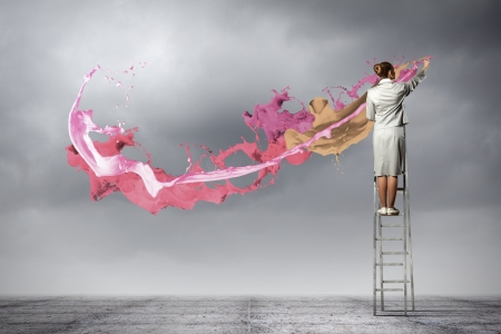Young woman standing on ladder drawing splashes with finger Imagens