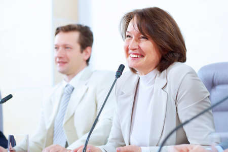 Image of two businesspeople sitting at table at conference speaking in microphone Stock Photo - 17760113