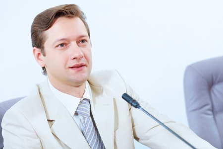 Image of young businessman sitting at table at business meeting photo