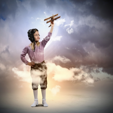 Image of little girl in pilots helmet playing with toy airplane against clouds background photo