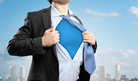 pulling: Image of young businessman showing superhero suit underneath his shirt standing against city background Stock Photo