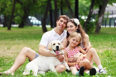 family day: Young Family Outdoors in summer park with a dog