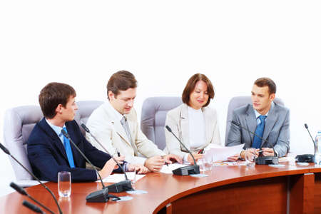 Image of four businesspeople discussing at meeting