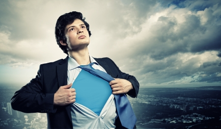 open shirt: Image of young businessman showing superhero suit underneath his shirt standing against city background Stock Photo