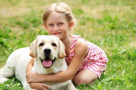 cani che giocano: Una bambina bionda con i suoi outdooors del cane da compagnia nel parco