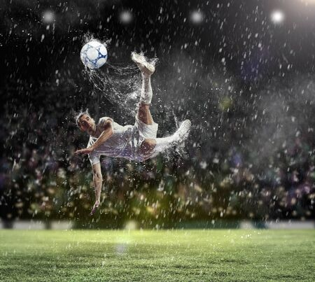 football player in white shirt striking the ball at the stadium under the rain Stock Photo - 17760492