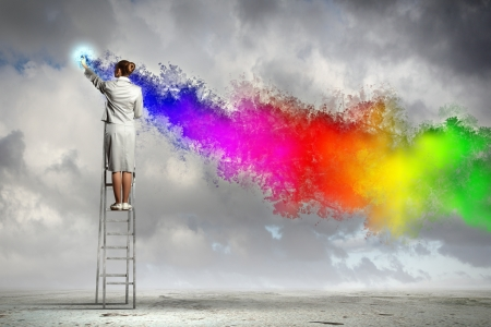 Young woman standing on ladder drawing splashes with finger Stock Photo