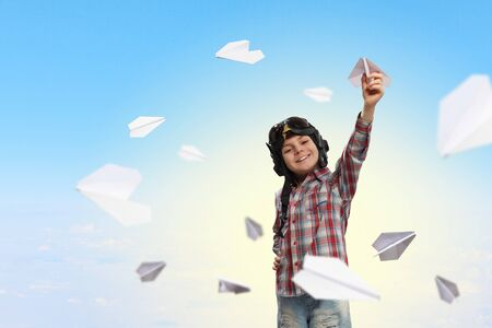 inair: Image of little boy in pilots helmet playing with paper airplane Stock Photo