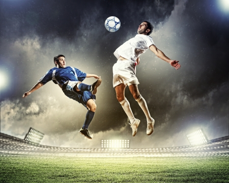 aloft: two football players in jump to strike the ball at the stadium