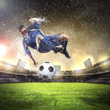 fast foot: football player in blue shirt striking the ball aloft at the stadium under the rain