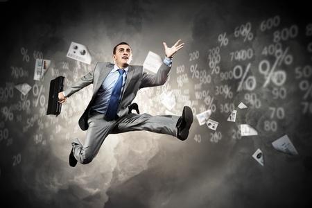 Image d'un homme d'affaires sautant haut sur le fond financier