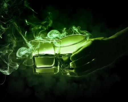 going out: Titolari di uno dei due bicchieri di assenzio verde Mano con fumi di uscire