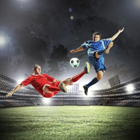 shoot: two football players in jump to strike the ball at the stadium