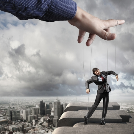 Businessman marionette on ropes controlled by puppeteer against city background photo