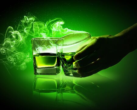 ajenjo: Mano que sostiene uno de los dos vasos de absenta verde con humo saliendo Foto de archivo