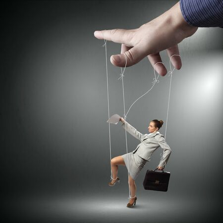 tiedup: Businesswoman marionette on ropes with suitcase in hand Stock Photo