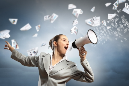 businesswoman in grey suit screaming into megaphone Stock Photo - 17769674
