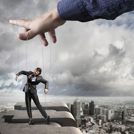 marioneta: Empresario marioneta con cuerdas controladas por titiritero contra el fondo de la ciudad