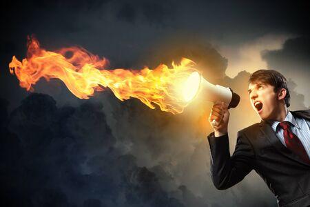 demon: młody biznesmen w czarny garnitur z krzykiem w megafon