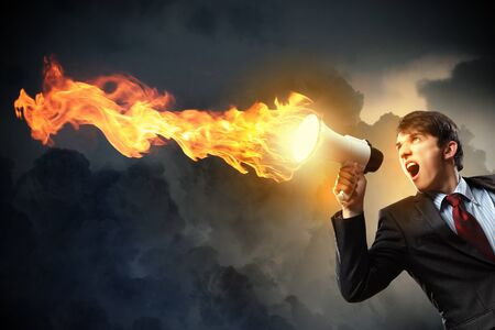 young businessman in black suit screaming into megaphone Stock Photo