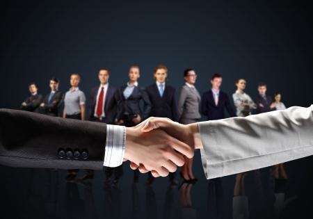 business handshake: business handshake against black background and standing businesspeople Stock Photo