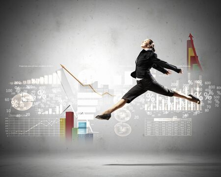 corporate vision: Image of pretty businesswoman jumping high against financial background Stock Photo