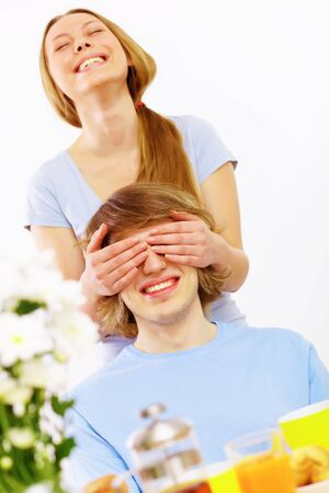 Young couple at home together - closing partner s eyes photo