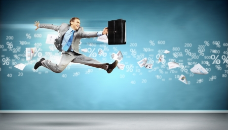 Image of a businessman jumping high against financial background photo