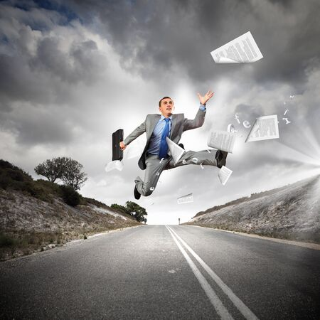 Young businessman in suit running on the road photo