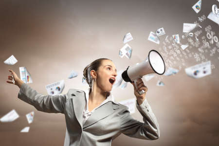 businesswoman in grey suit screaming into megaphone Stock Photo - 17821422