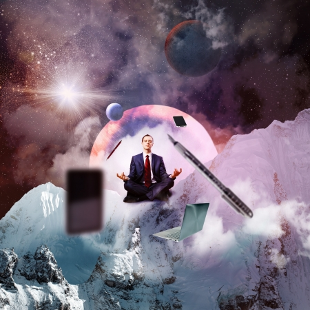 aloft: Businessman sitting in lotus flower position against space background with office stuff aloft
