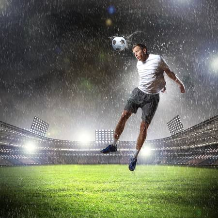 football player in white shirt striking the ball with head at the stadium under the rain photo