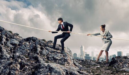 atop: Image of busionessman and businesswoman pulling rope atop of mountain Stock Photo