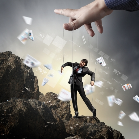 manipulate: Businessman marionette on ropes controlled by puppeteer standing atop of mountain