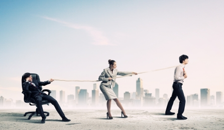 team effort: Image of three businesspeople pulling rope against city background