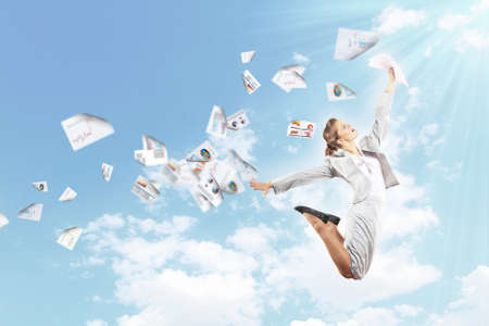 Image of a businesswoman jumping high against blue sky background photo