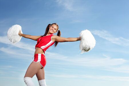 Young beautiful female cheerleader in uniform jumping high Stock Photo - 17867749