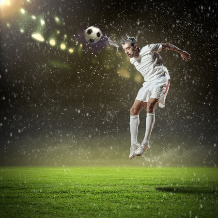 fast foot: football player in white shirt striking the ball with head at the stadium under the rain Stock Photo