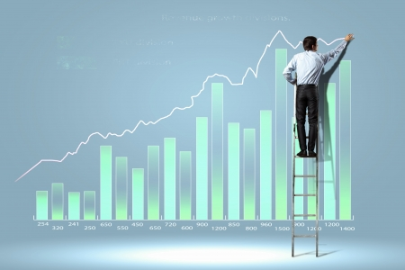 businessman standing on ladder drawing diagrams and graphs photo