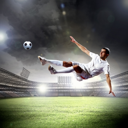 football player in white shirt striking the ball at the stadium photo